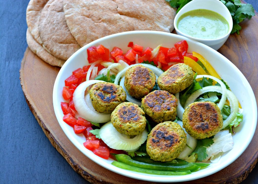 Try these {VEGAN} Baked Falafel smothered in a spicy Cilantro Yogurt Sauce all stuffed into a warm Pita bread pocket!